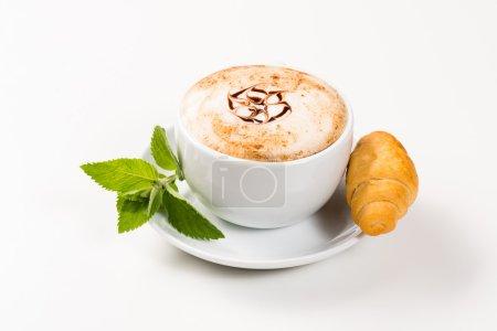 Photo pour Grande tasse de café avec un motif sur les mousses et les croissants, un petit déjeuner matinal - image libre de droit
