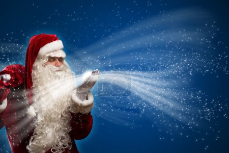 Photo for Santa claus blows with hands magic sparks holds on shoulder bag with Christmas presents - Royalty Free Image