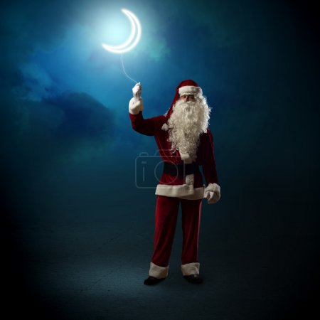 Photo for Santa Claus holding a string of luminous glowing moon - Royalty Free Image