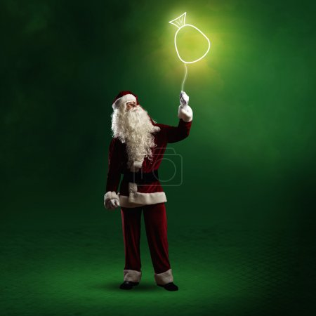 Photo for Santa Claus is holding a shining symbol of the bag with gifts on a string - Royalty Free Image