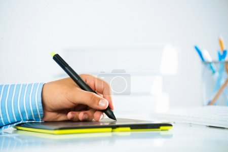 man's hand with a pen stylus
