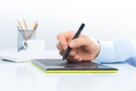 Designer hand on the tablet