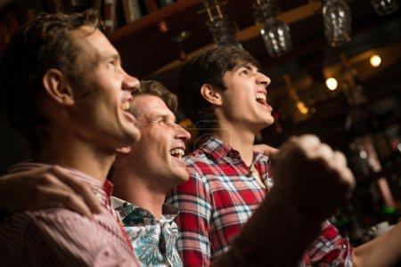 Photo pour Trois hommes debout dans un sourire embrassant rangée et regardez devant vous, les amateurs de sport - image libre de droit