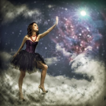 Photo for Young woman reaching for a glowing star, around abstract background - Royalty Free Image