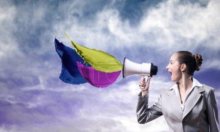 Photo pour Femme d'affaires criant dans un mégaphone, éclaboussure de peinture de couleur - image libre de droit