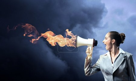 Business woman shouting into a megaphone