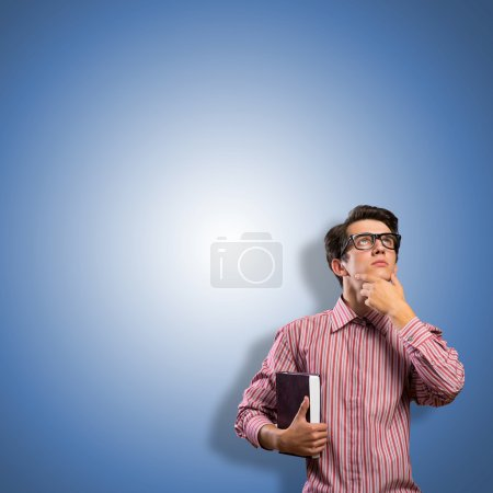 Photo for Young man scientist in glasses thinking, looking up - Royalty Free Image