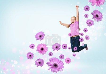 Photo pour Drôle fille sautant autour des points colorés et des fleurs - image libre de droit