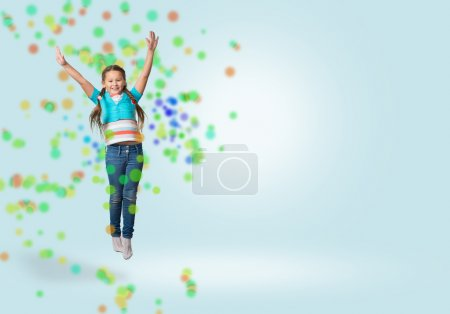 Photo for Funny girl jumping around colored dots and rays of light - Royalty Free Image