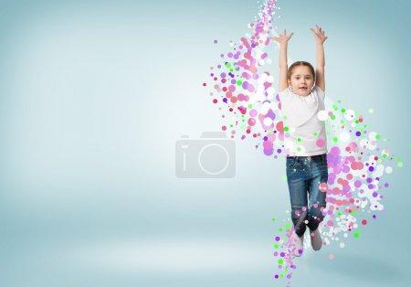 Photo pour Fille drôle sautant autour des points colorés et des rayons de lumière - image libre de droit