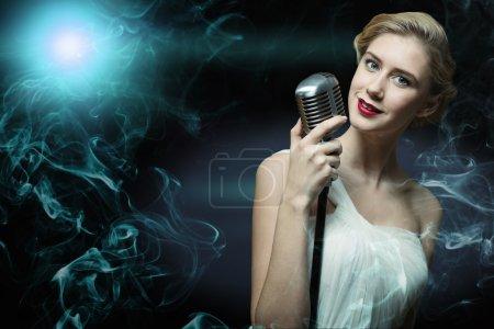 Photo pour Jolie chanteuse avec un microphone derrière son fond abstrait - image libre de droit