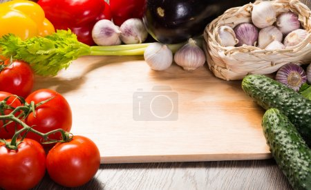 Photo for Tomatoes, cucumber, garlic, fresh herbs on chopping board - Royalty Free Image