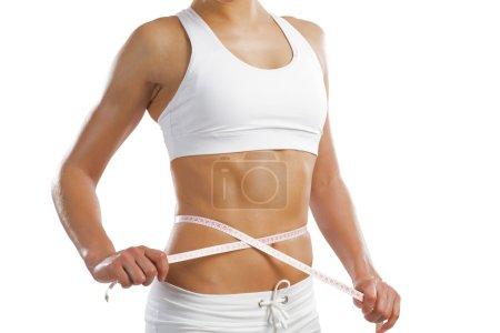Photo pour Jeune femme sportive mesurant la taille, isolée sur fond blanc - image libre de droit