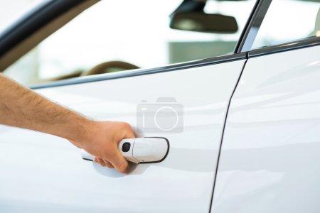 Photo pour L'homme ouvre la porte à une nouvelle voiture, l'inspection des wagons dans la salle d'exposition - image libre de droit