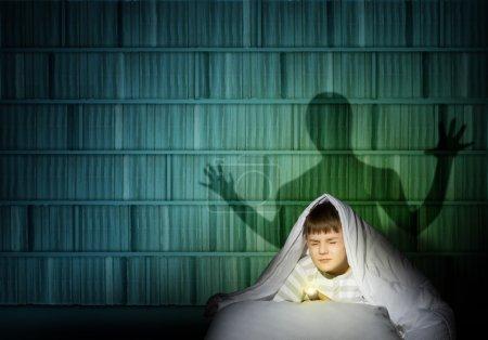 Photo pour Image d'un garçon sous les couvertures avec une lampe de poche la nuit peur des fantômes - image libre de droit