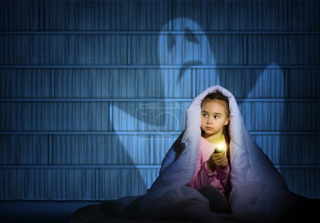 Photo for Image of a girl under the covers with a flashlight the night afraid of ghosts - Royalty Free Image
