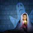 Image of a girl under the covers with a flashlight...