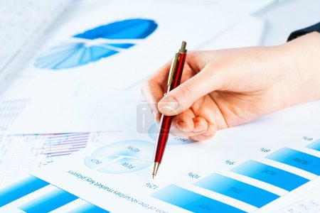Photo for Image of a female hand pointing to the financial growth charts - Royalty Free Image