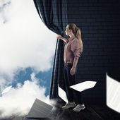young woman pushes the curtain looking at clouds