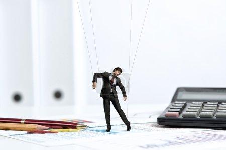 Photo pour Poupée marionnette homme d'affaires est sur le bureau, passé les articles de papeterie - image libre de droit