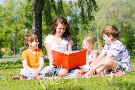 Photo pour Enfants et enseignants lisant ensemble dans le parc d'été - image libre de droit