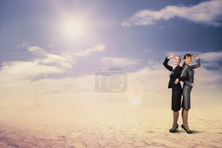Photo for Two business women holding hands, looking in different directions, teamwork - Royalty Free Image