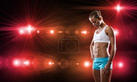 Photo pour Femme de sport en short et haut exercice au stade - image libre de droit