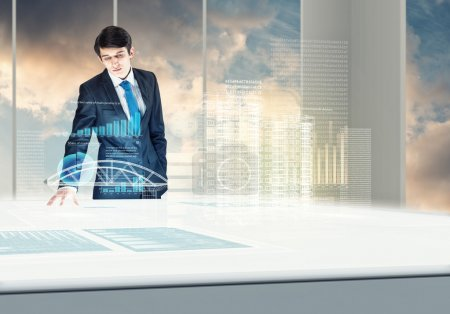 Photo for Young businessman looking at hologram of construction project - Royalty Free Image