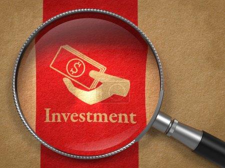 Photo pour Concept d'investissement : loupe avec investissement de mot et l'icône d'argent dans la main sur vieux papiers avec l'arrière-plan de la ligne verticale rouge. - image libre de droit