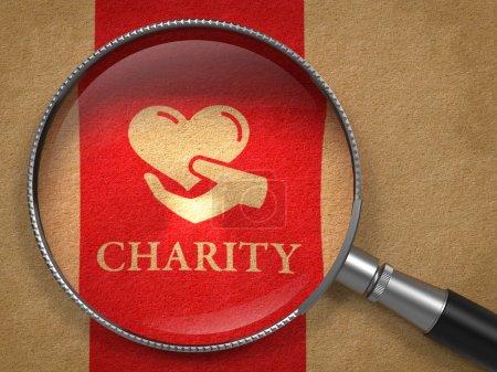 Photo pour Notion d'organisme de bienfaisance : loupe avec l'icône du coeur dans la main et le mot de la charité sur vieux papier avec l'arrière-plan de la ligne verticale rouge. - image libre de droit
