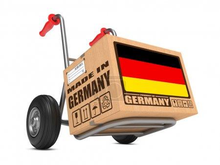 Photo pour Boîte en carton avec le drapeau de l'Allemagne et fait le slogan Allemagne quant à fond de camion blanc. livraison gratuite concept. - image libre de droit
