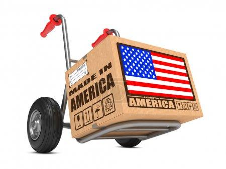 Photo pour Boîte en carton avec drapeau des États-Unis et fabriqué en Amérique Slogan sur fond blanc camion main. Concept de livraison gratuite . - image libre de droit
