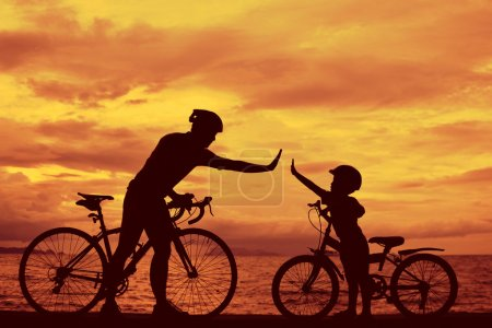 Photo for Biker family silhouette , daddy and son at the beach at sunet. - Royalty Free Image