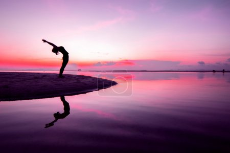 Photo for Silhouette woman with yoga posure on the beach at sunset with reflection. - Royalty Free Image