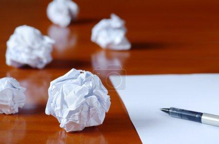 Photo pour Papier boules et stylo sur feuille blanche vierge - concept de crise de créativité - image libre de droit