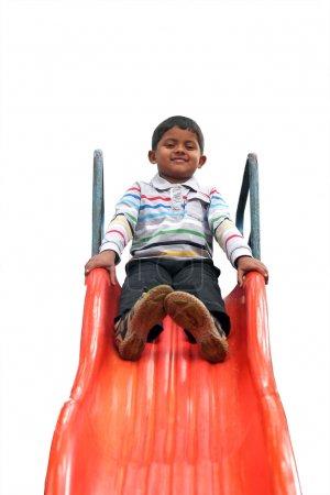 Photo pour Photo isolée d'un beau garçon indien (gamin) en slider dans un parc. La photo isolée avec fond blanc & chemin de coupure montre aire de jeux de l'heure d'été avec un écolier jouant sur un curseur - image libre de droit