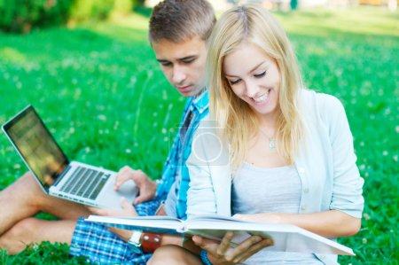 Photo pour Étudiants heureux avec le livre et l'ordinateur portable dans le parc - image libre de droit