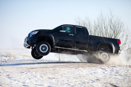 Black truck traveling in the snow and jumping