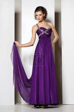 Young beautiful brunette in purple dress on white