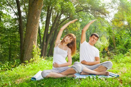 Young man and woman doing yoga in garden