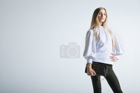 Photo for Full length casual young fashionable woman with a bag in light background - Royalty Free Image
