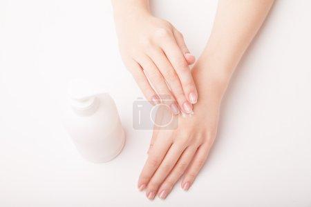 Photo pour Gros plan de belle main féminine appliquant crème pour les mains - image libre de droit