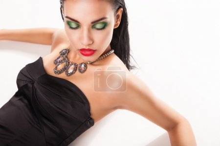 Beautiful woman in jewellery laying over white