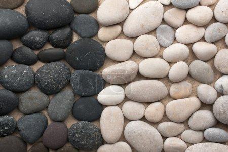 Photo pour Pierres noires et blanches se trouvent côte à côte sur le sable - image libre de droit