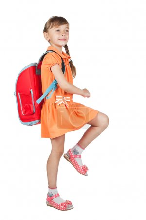 Baby girl with backpack goes to school