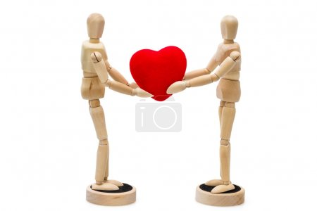 Two wooden dolls, mannequins holding red heart over a white back