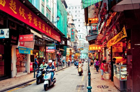 Narrow crowded street with many shops and restaurants in the centre of Macau.