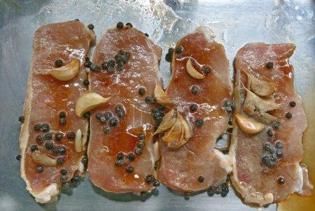 Photo pour Steak de porc cru avec l'ail et poivre noir - image libre de droit