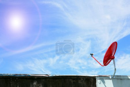 isolated red satellite on sunny blue sky