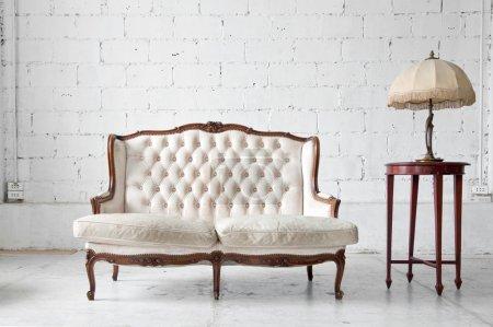 Photo pour Canapé classique en cuir véritable blanc dans une pièce vintage avec lampe de bureau - image libre de droit